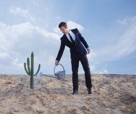 Man watering the cactus Stock Photo