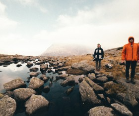 Men standing on calm lake stones Stock Photo