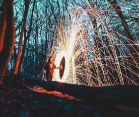 Person with sparkling fireworks in forest Stock Photo