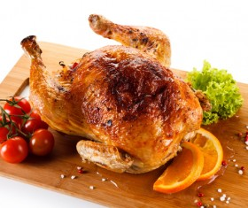 Roasted whole chicken with tomatoes on the chopping block Stock Photo
