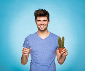 Smiling man ready to water the cactus Stock Photo