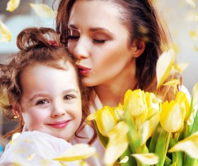 Smiling mother kissing daughter Stock Photo