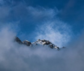 Thick cloud covering snowy peak Stock Photo