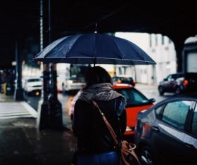 Woman walking under rainy weather with umbrella Stock Phot