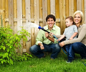 Young couples with children to water the plants Stock Photo