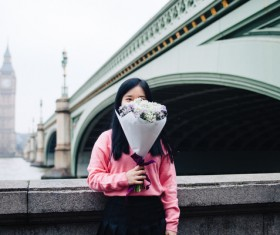 Young girl posing with flowers in classical city Stock Photo