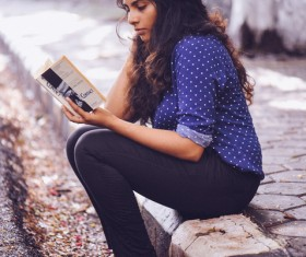 Young woman reading book on pavement Stock Photo
