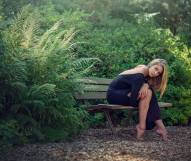 Beautiful girl sitting on a bench outdoors Stock Photo