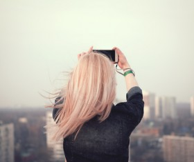 Blonde girl taking picture of the cityscape Stock Photo