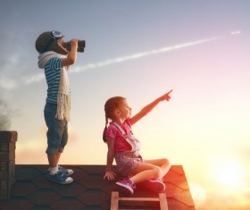 Children on the roof looking at planes Stock Photo