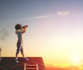 Children on the roof with a telescope to see the plane Stock Photo