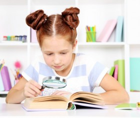 Children reading books with magnifying glass Stock Photo