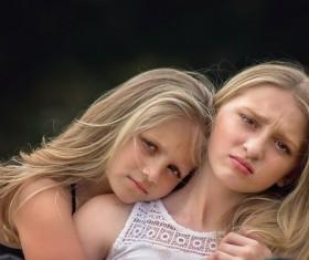 Cuddling sisters Stock Photo
