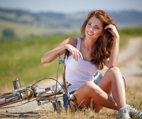 Girl sitting on the roadside to rest and bicycles Stock Photo