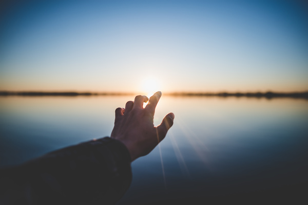 Hand posing with sunlight on calm river Stock Photo
