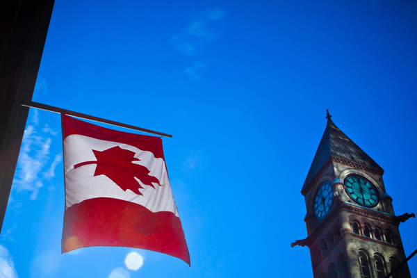 Hanging Canadian flag and clock tower Stock Photo