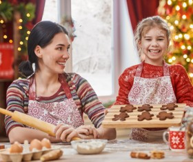 Happy daughter and mother making Christmas food Stock Photo