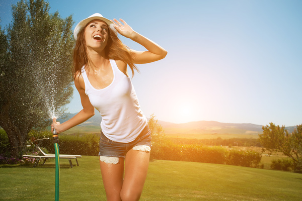 Happy girl watering the lawn Stock Photo 01