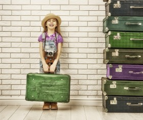 Happy little girl holding a suitcase Stock Photo
