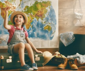 Little girl playing with toy airplane sitting on the table Stock Photo