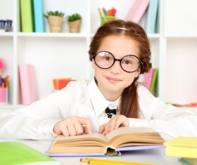 Little girl reading with glasses Stock Photo