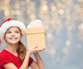 Little girl wearing a christmas costume is holding gift box