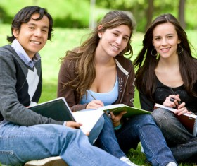 Male and female students sitting in the grass Stock Photo 01
