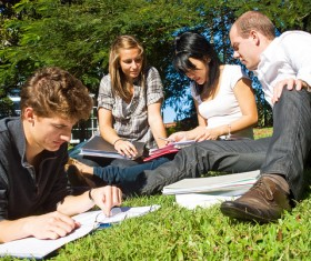Male and female students sitting in the grass Stock Photo 02
