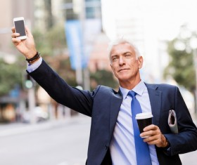 Man holding cellphone and coffee takes taxi Stock Photo