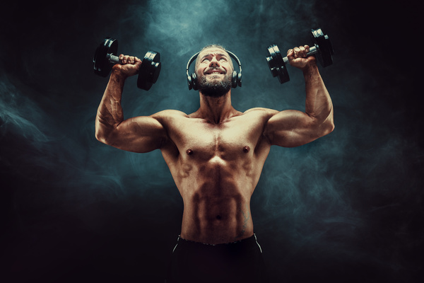 Men lifting dumbbells with headphones