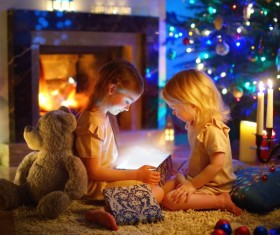 Open gift box under Christmas tree Little Sisters Stock Photo
