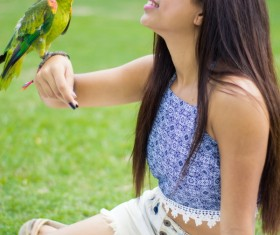 Parrot standing on the girls arm Stock Photo