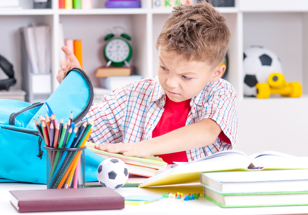 Pupils who take out books from their schoolbags Stock Photo