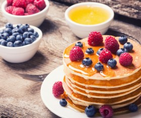 Raspberry blueberry pancakes with honey Stock Photo