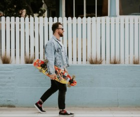 Stylish man walking with skateboard Stock Photo