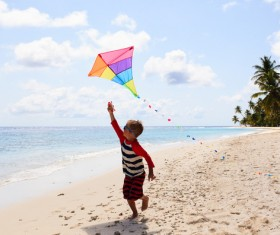 The little boy flying the kite on the beach Stock Photo