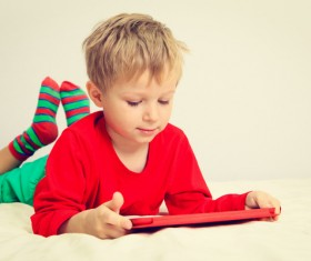 The little boy who plays the game on the bed Stock Photo