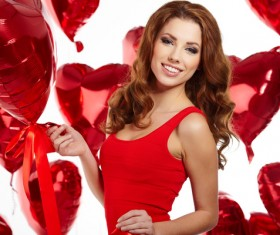 Woman holding heart-shaped balloon smiling Stock Photo