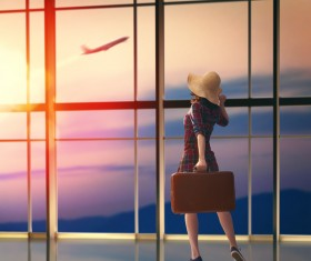 Woman holding travel bag in departure lounge Stock Photo