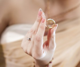 Woman holding wedding ring in hand Stock Photo
