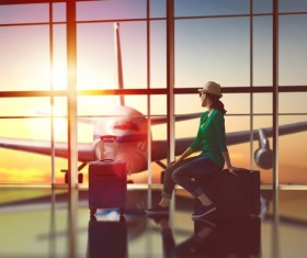 Woman sitting in suitcase looking at the plane in the distance Stock Photo