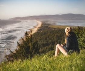 Woman sitting on the hillside watching the sea Stock Photo