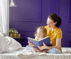Young mother and daughter read together Stock Photo 02