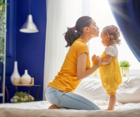 Young mother kissing daughter Stock Photo