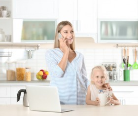 Young mothers calling in the kitchen Stock Photo 02