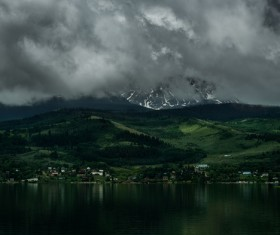 cloudscape above calm mountain lake scene Stock Photo