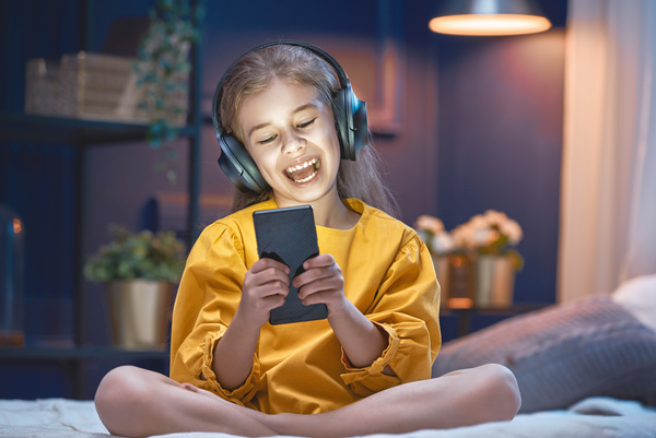 little girl listens to music with her Smartphone Stock Photo