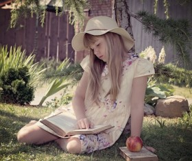 little girl sitting on the grass reading Book Stock Photo
