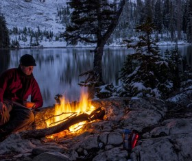man resting beside the campfire Stock Photo