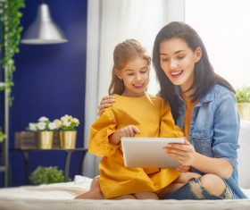 mother and her daughter girl are playing with tablet Stock Photo 04